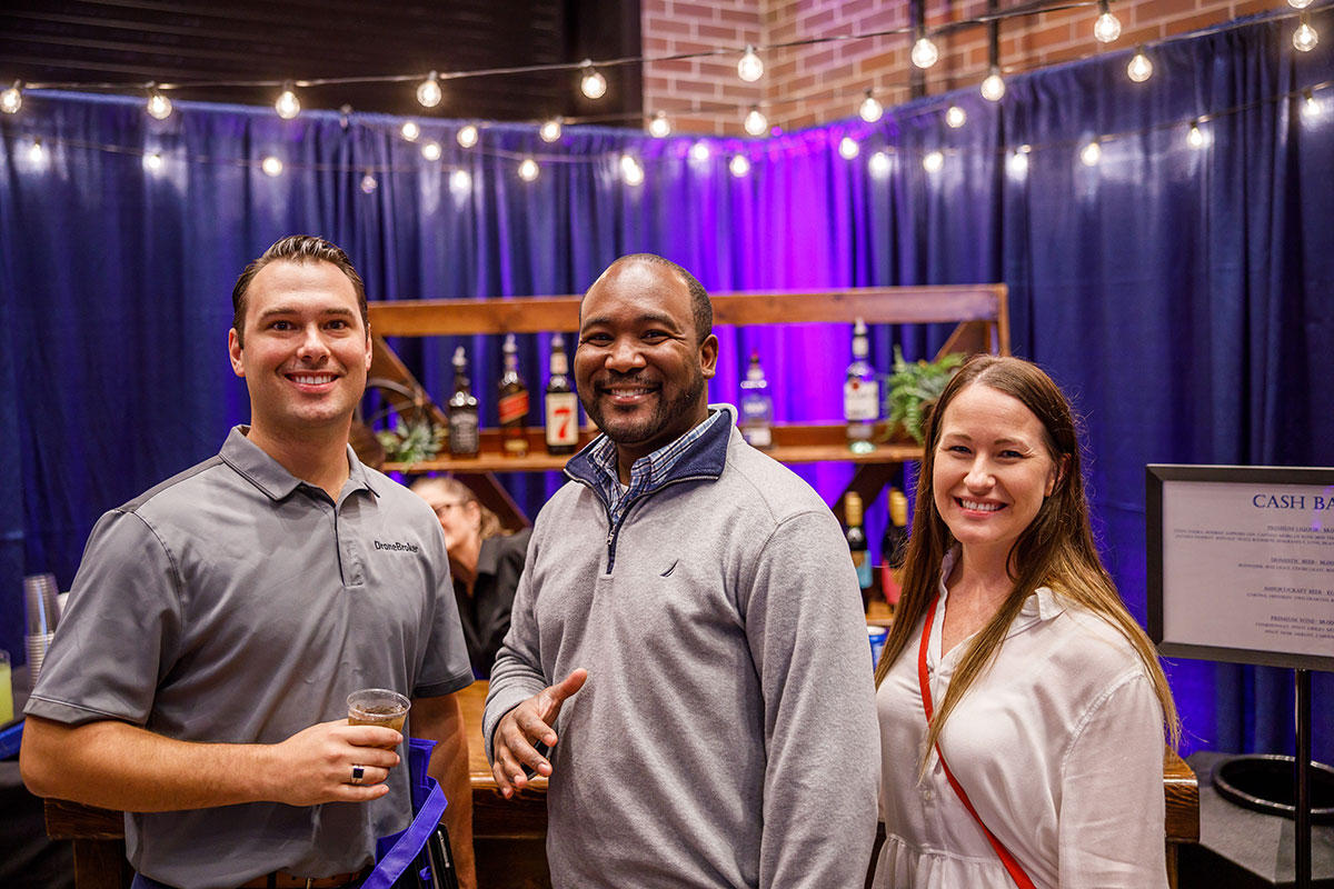 three people smiling at job fair booth in South Bend